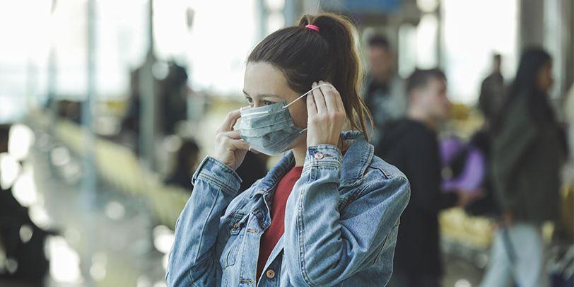 Frau zieht Schutzmaske über Gesicht
