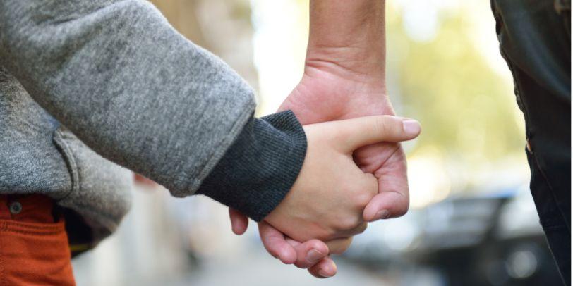 Vater hält Kind an der Hand