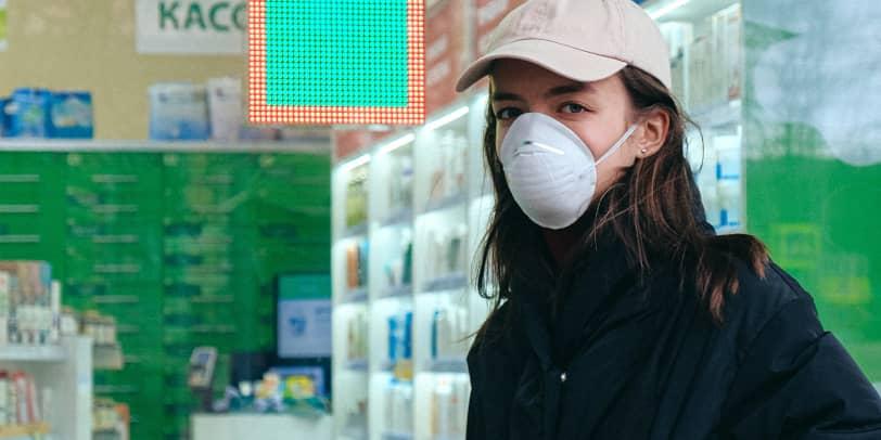 Frau mit FFP2-Maske steht vor Apotheke