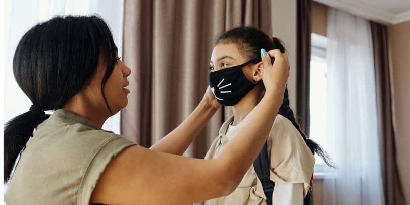 Frau zieht Kind eine Maske auf