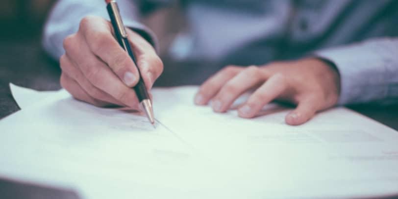 Mann schreibt auf Dokumenten